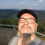 """Verschwitzt auf dem Aussichtsturm auf dem """"Großen Knollen"""". Im Hintergrund ist der höchste Berg des Harz, der Brocken (1141m) zu sehen. Also so in der Ferne, ganz klein, links neben meinem werten Schädel."""
